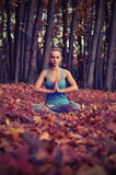 Young woman meditating in autumn forest. Young blond woman in blue t-shirt practicing yoga sitting on the ground in the half-lotus position meditating with Royalty Free Stock Image