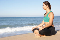 Young Woman Meditating On Beach Stock Photos