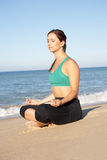 Young Woman Meditating On Beach Stock Images