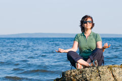 Young woman meditating on the beach. Young brunette woman with sunglasses meditating on the beach, yoga pose, sitting on rock Stock Image