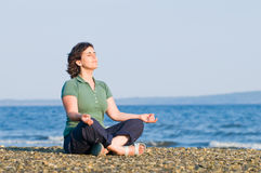 Young woman meditating on the beach. Young brunette woman meditating on the beach, yoga pose, sitting on pebbles Stock Image