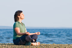 Young woman meditating on the beach. Young brunette woman meditating on the beach, yoga pose, sitting on pebbles Stock Photo