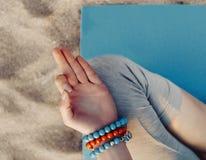 Young woman meditating on beach. Stock Photos
