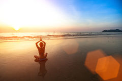 Young woman meditating on the beach Sea at sunset. Royalty Free Stock Photography