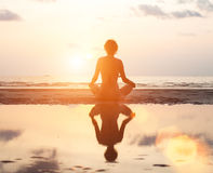 Young woman meditating on the beach at sunset. Stock Images