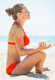 Young woman meditating on beach Royalty Free Stock Photos