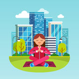 Young woman meditating at the big city park. Young woman meditating in contemplation sitting on the grass in lotus yoga pose at the big city park. Girls hands Royalty Free Stock Photography