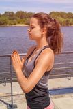Young woman meditating in city by the river in summer, closed ey Stock Photo