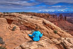 Young woman meditating at cliff by Mesa Arch. Canyonlands National Park. Moab. Utah. United States Stock Photos
