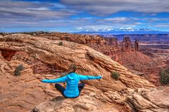 Young woman meditating at cliff by Mesa Arch. Stock Photo