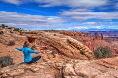 Young woman meditating at cliff by Mesa Arch. Canyonlands National Park. Moab. Utah. United States Royalty Free Stock Image