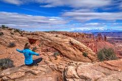 Young woman meditating at cliff by Mesa Arch. Royalty Free Stock Image