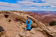Young woman meditating at cliff by Mesa Arch. Canyonlands National Park. Moab. Utah. United States Stock Photo