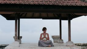 Woman meditating and doing yoga in abandoned temple. Female practicing pose stock video