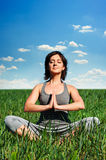 Young woman meditating on the field Royalty Free Stock Photos