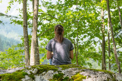 Young woman meditating on forest rock. Stock Photos