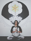 Young woman meditating in front of large mandala painting on the wall. Stock Images
