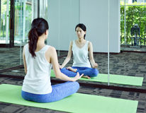 Young woman meditating in front of mirror in yoga room, Yoga con Stock Photo