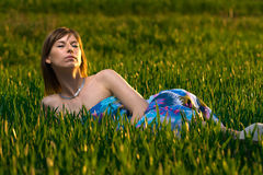 Young woman meditating in a green field Stock Images
