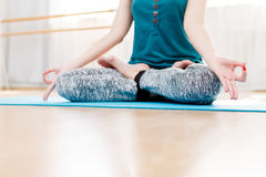 Young woman meditating in the gym, lotus asana. Young woman meditating in the gym, in lotus position Royalty Free Stock Image