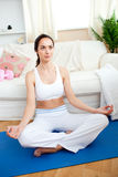 Young woman meditating in her living-room Royalty Free Stock Image