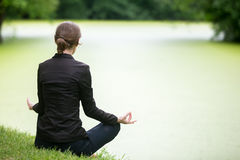 Young woman meditating on lake Stock Images