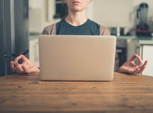 Young woman meditating by laptop Royalty Free Stock Photos
