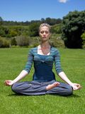 Young woman meditating on a lawn.  Stock Image