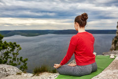 Young woman meditating in a lotus pose on the rock above big river. Sporty woman in the red sports jacket, leggings and barefoot. Beautiful landscape like a Royalty Free Stock Photo
