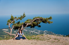 Young woman meditating in lotus position while doing yoga under the tree on the top of the mountain. Travel, Healthy Stock Photography
