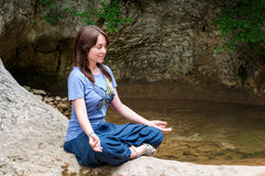 Young woman meditating in lotus position while doing yoga in a wonderful forest near waterfall. Travel, Healthy Royalty Free Stock Image