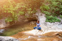 Young woman meditating in lotus position while doing yoga in a wonderful forest near waterfall. Travel, Healthy Stock Photography