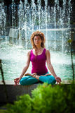 Young woman meditating in lotus position Stock Photos