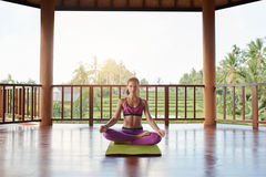 Young woman meditating in lotus yoga pose Stock Photo