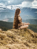 Young woman meditating in mountains Stock Photo