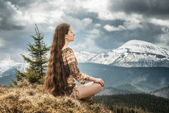 Young woman meditating in mountains Stock Photos