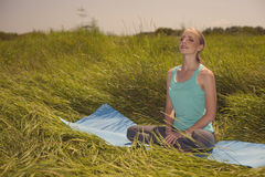 Young woman meditating on the nature with eyes closed Royalty Free Stock Photography