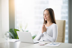 Young woman meditating near laptop Stock Photo