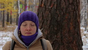 Young woman meditating near the old large tree in the winter forest. Close-up stock video footage