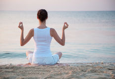 Young woman meditating near the sea Stock Photo