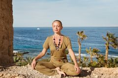 Young woman meditating near the sea Royalty Free Stock Photography