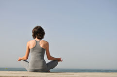 Young Woman Meditating On The Beach Stock Photos