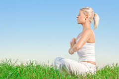 Young woman meditating outdoors Stock Images