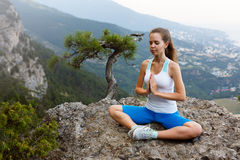 Young woman meditating outdoors, girl doing yoga high in the mountains, relaxation self-reflection concept Stock Photo