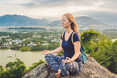 Young woman meditating over ancient city landscape on sunrise Co Stock Images