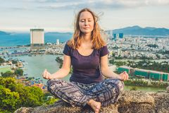 Young woman meditating over ancient city landscape on sunrise Copy space Stock Image