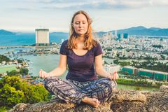 Young woman meditating over ancient city landscape on sunrise Copy space royalty free stock photography