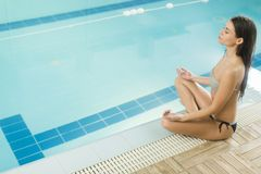 Young woman meditating by the pool Royalty Free Stock Photography