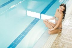 Young woman meditating by the pool Stock Photos