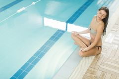 Young woman meditating by the pool Royalty Free Stock Image